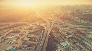 Aerial Drone Flight Footage of highway and overpass with cars and trucks. Camera Flies Over the Road Junction in the big city. Top view. Cityscape in sunset soft light. Instagram vintage filter toning
