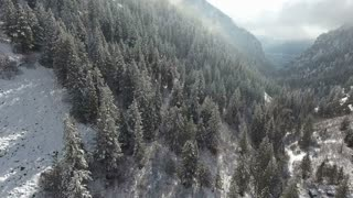 Aerial drone flying forward through clouds and snow covered canyon in the mountains