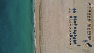 Aerial drone flyover cinemagraph of symmetrical beach front line with cabanas and umbrellas lined up, minimalistic resort view, calm paradise like maldives travel destination, waves and ocean