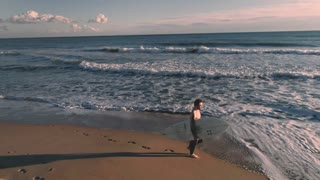 Aerial drone footage of casual and relaxed professional and experienced surfer in wet suit walk on beach at sunset, watching waves and enjoying warm sun and nature. Summertime mood