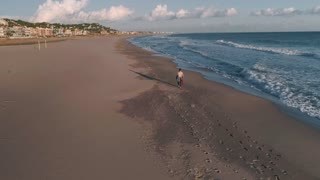 Aerial drone footage of lonely surfer in wetsuit walk on empty and deserted sandy beach, looks at waves and horizon on beautiful sunset. Travel destination abroad for healthy lifestyle
