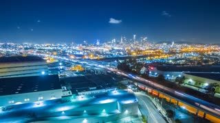 Aerial evening timelapse in motion or hyperlapse facing downtown Los Angeles after sunset with stunning deep blue sky buildings, and car lights with traffic on a street with traffic below.