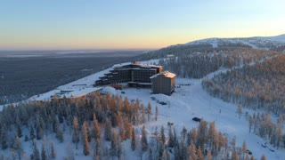 AERIAL: Flying around hilltop skiing resort surrounded by ski slopes in winter