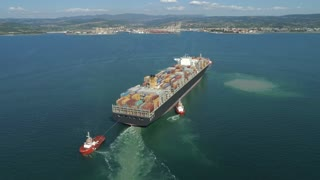 AERIAL: Flying around large container ship approaching a shipyard on the coast.