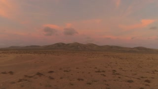 AERIAL: Flying away from big volcanic structure in pink colored desert sunset.