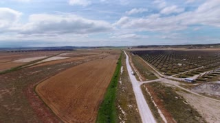 Aerial footage following industrial company truck riding through gravel offroad road near field of solar panels producing renewable energy of sun, beautiful sunny day with blue sky and clouds
