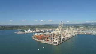 AERIAL: Giant industrial terminal of an international ocean port on green coast.