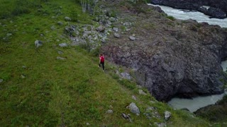 Aerial. girl traveler with backpack walks along the cliff in the mountains. woman tourist went Hiking. Altai, Siberia. Aerial camera shot