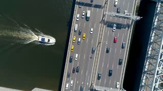 Aerial high angle of a boat moving under the bridge.