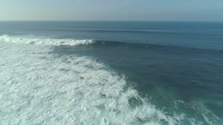 AERIAL: Hovering above unrecognizable surfboarders lining up and riding waves.