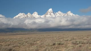 AERIAL: Majestic Grand Teton mountains raising above the foggy clouds in Wyoming