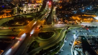 Aerial motion timelapse or hyper lapse at night over a traffic circle onramp and up a street showing streaks of car lights, city buildings and parking lots, indicative of the fast paced city lifestyle