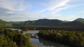 Aerial panorama of the green forest and river near mountains. Altai, Siberia. Aerial camera shot