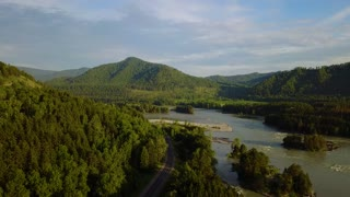 Aerial. panorama of the green forest and river near mountains. Altai, Siberia. Aerial camera shot