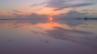 AERIAL Pink sky and golden setting sun reflecting in ocean surface in salt flats