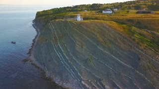 Aerial shot of lighthouse on sand dune and sea view