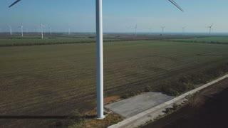 Aerial shot of rotating wind turbines on farmland near ocean