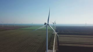 Aerial shot of the rotating wind turbines in the field with wheat