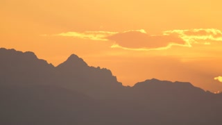 AERIAL: Silhouette of mountaintops in majestic European Alps over sky at sunset
