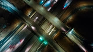 Aerial time lapse at night from above a Los Angeles highway with a cinematic and futuristic look at the urban or city traffic and on and off ramp traffic circles below.