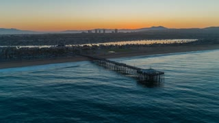 Aerial time lapse in motion (hyper lapse) at sunrise over the Newport Beach Balboa pier and harbor with boats, yachts, coastal beach homes, palm trees and urban skyline in view.