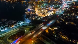 Aerial time lapse in motion or hyper lapse at night over a busy traffic circle onramp and up street showing streaks of car lights, city buildings and parking lots. Fast paced city life with moon reflection on harbor water.