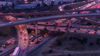 Aerial time lapse of cars and trucks on freeway and highway with lights in heavy traffic at sunset