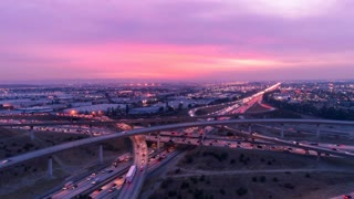 Aerial time lapse of cars on freeway and highway with lights in heavy traffic at sunset