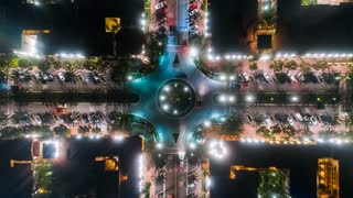 Aerial time lapse or hyper lapse at night with a cinematic and futuristic look at an urban traffic circle or intersection with cars below.