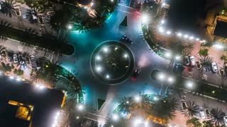 Aerial time-lapse or hyper-lapse at night with a cinematic look at an urban traffic circle intersection with cars driving below.