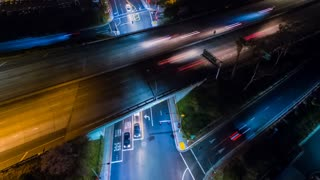Aerial timelapse at night with a freeway and intersection with traffic in view