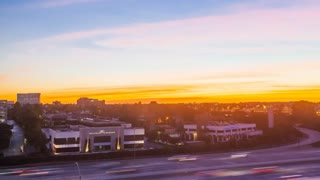 Aerial timelapse in motion along city freeway at sunset with tall buildings, city traffic, blue and orange skies.