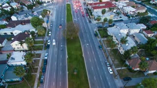 Aerial timelapse in motion at twilight at residential neighborhood intersection with traffic, stoplights and homes