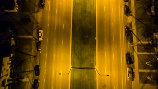 Aerial timelapse in motion (hyperlapse) at night with a cinematic look at a suburban Los Angeles freeway and neighborhood intersection with traffic below.