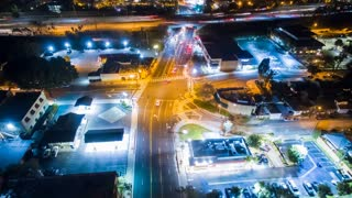 Aerial timelapse in motion (hyperlapse) at night with a cinematic look at an urban Los Angeles interstate and intersection with traffic