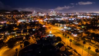 Aerial timelapse in motion (hyperlapse) at night with a cinematic look at an urban Los Angeles neighborhood and intersection with traffic.