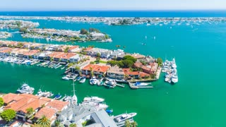 Aerial timelapse in motion (hyperlapse) over Newport Beach harbor with Linda Isle and Bay Isle islands, boats, yachts, oceanfront coastal homes, blue sunny skies, Pacific ocean and Catalina Island in the background.