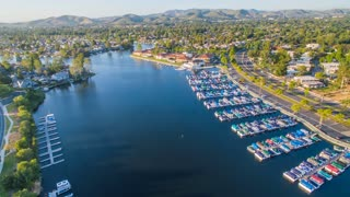 Aerial timelapse in motion (hyperlapse) over the Westlake Village lake with boats, luxury homes, trees, traffic, mountains and blue sunny skies in the background