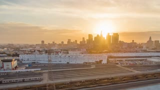 Aerial timelapse in motion (hyperlapse) shot at sunset facing downtown Los Angeles at twilight or sunset with the sky changing from day to night with stunning yellow and gold skies. In foreground are buildings and trains.