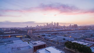 Aerial timelapse in motion (hyperlapse) shot at sunset facing downtown Los Angeles at twilight with the sky changing from day to night with epic pink skies and clouds above and traffic on a busy street below.