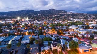 Aerial timelapse in motion (hyperlapse) shot at sunset in Los Angeles at twilight with lightning mushroom clouds forming changing from day to night with mountains in the back and LA city traffic intersection and streets below.
