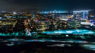 Aerial timelapse in motion or hyperlapse at night along the urban California I-405 interstate with cars, headlights, traffic and high rise buildings and the city skyline.