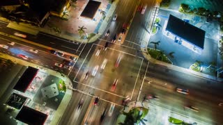 Aerial timelapse or aerolapse at night with a cinematic and futuristic look at an urban Los Angeles street intersection showing busy traffic from above.