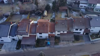 AERIAL TOP DOWN Flying over quiet frozen suburban town on cold winter day