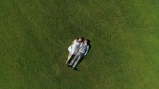 AERIAL TOP DOWN Happy parents to be relaxing side by side in field holding hands