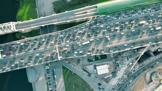 Aerial top down shot of heavy congested road traffic and moving commuter train in the rush hour. Private cars versus public transport concept. 4K video