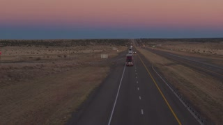 AERIAL: Traffic of freight semi trucks and cars driving along a highway at dawn