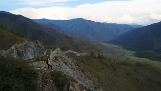 Aerial. traveler on the edge of the cliff enjoying the beautiful view. girl tourist in mountain. Altai, Siberia. Aerial camera shot