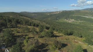 AERIAL: Vast green juniper forest surrounding rural village in the karst valley.