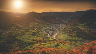 Aerial View: Beautiful canyon village located along the river. Dramatic autumn mountain landscape with green meadows, orange pine tree forests, sunset cloudy sky. Carpathians, Ukraine, Europe. 4K
